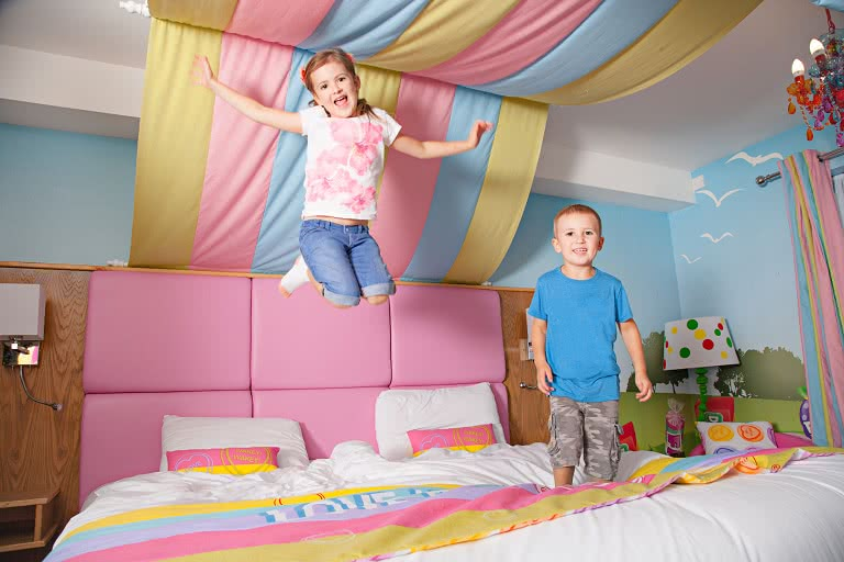 Two children bouncing on a bed in the Swizzels suite