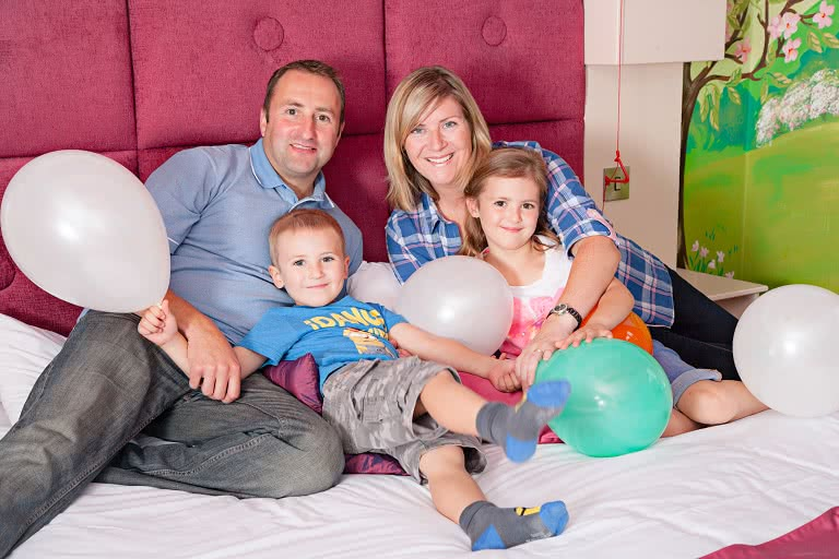A family with balloons on the bed in a princess suite